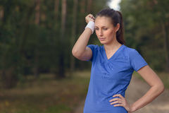 Woman athlete wiping sweat from her forehead Royalty Free Stock Images