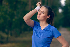 Woman athlete wiping sweat from her forehead. Onto her wristband as she pauses during her training exercises on a forest track Stock Photos
