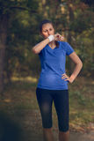 Woman athlete wiping sweat from her forehead. Onto her wristband as she pauses during her training exercises on a forest track Royalty Free Stock Image