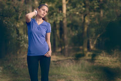 Woman athlete wiping sweat from her forehead Stock Photos