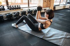 Woman athlete working out with abdominal muscles in gym. Slim young woman athlete working out with abdominal muscles in gym stock image