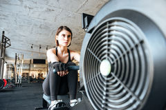 Woman athlete working out with training machine in gym Royalty Free Stock Photos