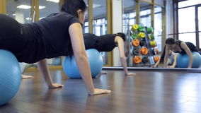 Woman athletes rock on gym ball press in fitness studio stock video footage