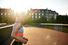Woman in athletic wear exercising outdoors. On an empty road by apartment houses Stock Image