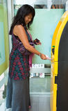 Woman at ATM. Asian woman withdrawing money at ATM Stock Image