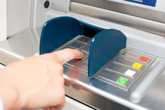 Woman at ATM or cash dispenser. And is entering her PIN; only hand to be seen Stock Photos