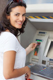 Woman at ATM. Hispanic woman smiling while withdrawing cash at ATM Stock Image