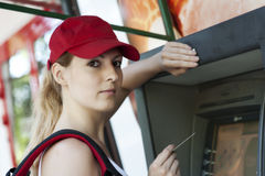 Woman and ATM machine. A young girl puts your card into an ATM machine Stock Photo