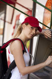 Woman and ATM machine. A young girl puts your card into an ATM machine Royalty Free Stock Images
