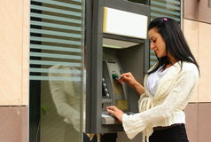 Woman at atm machine Stock Images