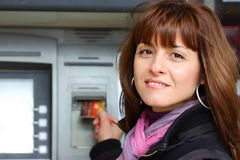 Woman at the ATM outdoor. Woman using an ATM machine looking at the camera outdoor closeup shot Stock Image
