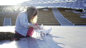Woman attach the propellers to the drone. Side view of casual young woman sitting on pavement in modern park and attach propellers to white modern drone in sun stock video footage