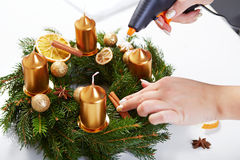 Woman attaches cinnamon on a Christmas wreath royalty free stock photo