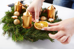 Woman attaches orange on Christmas wreath Stock Images