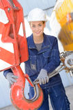Woman attaching wire to hook crane Stock Photos