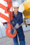 Woman attaching wire to winch crane Royalty Free Stock Photography