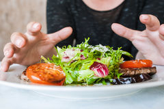 Woman attacks medallions with salad Stock Photography