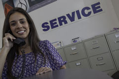 Woman attending a call at automobile repair shop Royalty Free Stock Image