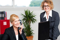Woman attending call with colleague beside her Stock Photography