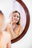 Woman attentively looking at herself in the mirror Stock Photos