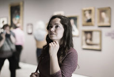 Woman attentively looking at paintings in art museum Royalty Free Stock Image