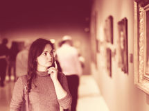 Woman attentively looking at paintings in art museum Royalty Free Stock Images