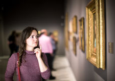 Woman attentively looking at paintings in art museum Royalty Free Stock Photography