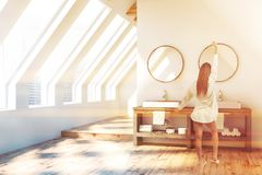 Attic bathroom, white double sink, woman. Woman in attic bathroom interior with white walls, wooden floor and white double sink standing on gray countertop with royalty free stock photo