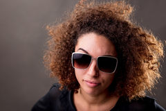 Woman with attitude. Portrait of attractive young multi-racial woman in sunglasses with frizzy, curly red hair and gentle smile, dark brown, background Stock Photography