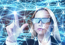 Woman in augmented reality glasses, network. Close up of a blond businesswoman in augmented reality glasses interacting with a network hologram. Abstract blue royalty free stock images