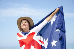Woman and Australian Flag. Portrait of Attractive mature woman wearing akubra hat and with Australian flag around shoulder posing  with blue sky as background Royalty Free Stock Photo