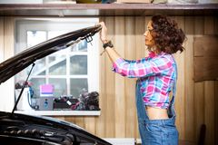 Woman auto mechanic in denim overalls opens or closes the car`s hood royalty free stock photos