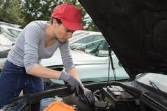 Woman auto mechanic fixing engine car outdoors. Woman auto mechanic fixing the engine of a car outdoors Stock Image