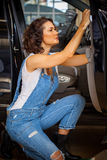 Woman auto mechanic in a garage. Beautiful woman auto mechanic in a blue denim overalls repairs a car door in a garage royalty free stock photo