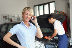 Woman in auto repair shop Stock Images