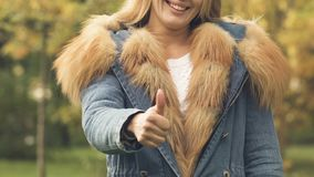 Woman in autumn coat with fur showing thumbs up, advertising warm clothes. Stock footage stock video
