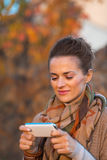 Woman in autumn evening outdoors writing sms Royalty Free Stock Images