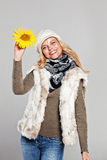 Woman in autumn fashion holding a sunflower and smiling Royalty Free Stock Photo