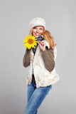 Woman in autumn fashion playing with a sunflower Stock Images