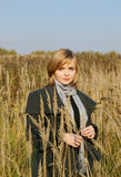Woman in autumn field with long grass Stock Photography