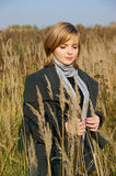 Woman in autumn field with long grass Royalty Free Stock Photography