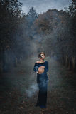 Woman in the autumn garden in the evening. She is holding a pumpkin Stock Images