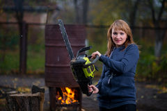 Woman in autumn home garden sawing wood. Middle aged woman in autumn home garden sawing wood Stock Image
