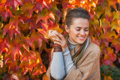 Woman with autumn leafs in front of foliage Royalty Free Stock Image