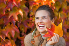 Woman with autumn leafs in front of foliage Stock Photo