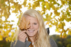 Woman with autumn leave Stock Images