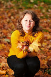 Woman in autumn leaves Stock Photos
