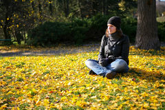 Woman on the autumn leaves Stock Photography