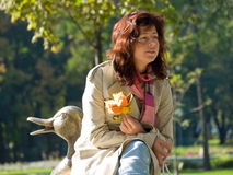 Woman with autumn leaves. In a park Royalty Free Stock Image
