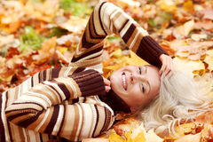Woman on autumn leaves Royalty Free Stock Image